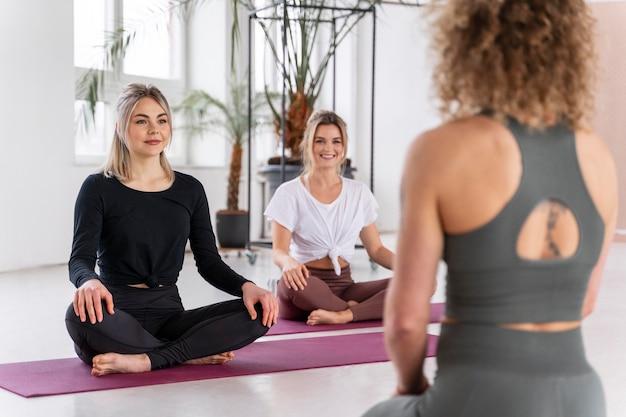 Feche a professora de ioga e as mulheres