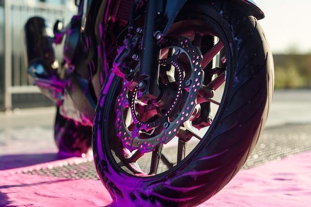 Feche a roda da motocicleta esportiva elegante com espuma na lavagem de carros self-service ao amanhecer.