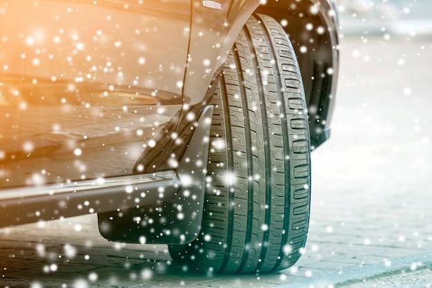 Feche a roda do carro de detalhes com o novo protetor de pneu de borracha preta na estrada coberta de neve de inverno. conceito de transporte e segurança.
