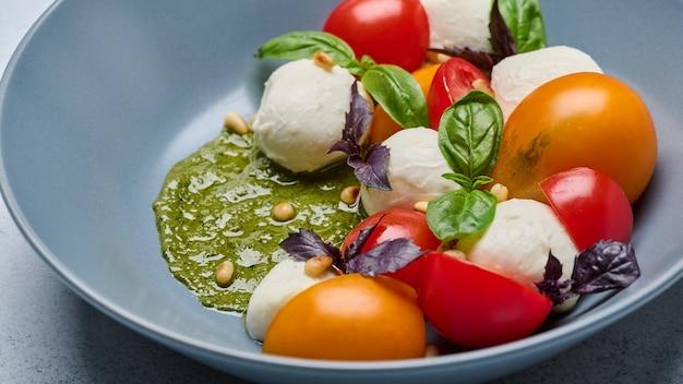 Feche a salada caprese italiana com tomates maduros, manjericão, nozes, pesto e queijo mussarela na cor cinza