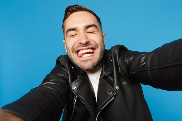 Feche a selfie do elegante jovem com barba por fazer em uma jaqueta de couro preta, camiseta branca, olhando a câmera isolada no retrato de estúdio de fundo de parede azul. conceito de emoções sinceras de pessoas. simule o espaço da cópia