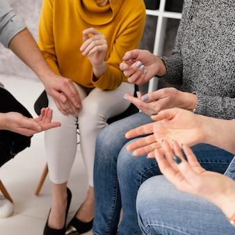 Feche a sessão de terapia de grupo com as mãos Foto gratuita