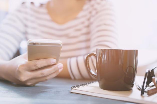 Feche a sessão feminina de pessoas usando smartphone móvel em uma pausa para relaxar. xícara de café na mesa da secretária com o bloco de notas do livro, óculos, suprimentos de equipamento no trabalho. copie o espaço. mulher de trabalho do conceito.