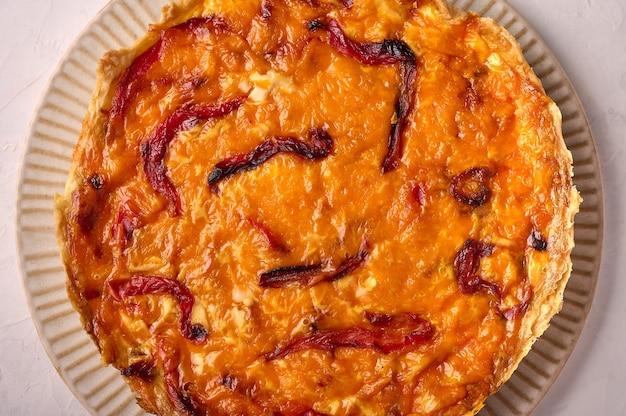 Feche a superfície da comida torta de quiche caseira com frango, tomate seco e queijo cheddar na luz