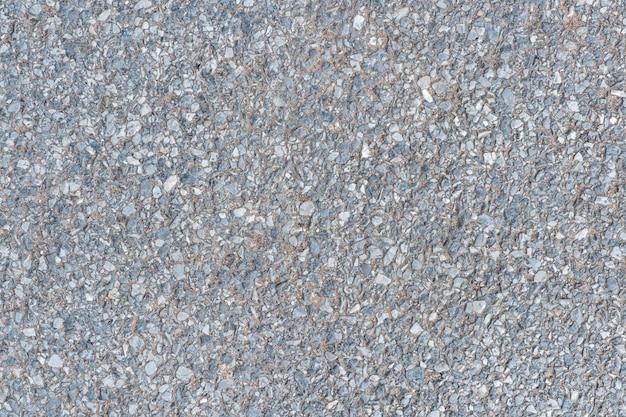 Feche a superfície da estrada com pedra de seixo no fundo de textura de piso de concreto