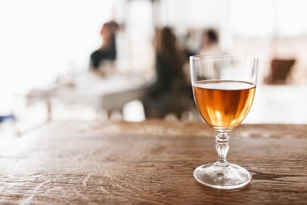 Feche a taça de vinho na mesa de madeira em uma cozinha aconchegante com fundo difuso isolado