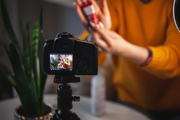 Feche a tela da câmera, mulher blogueira de beleza faz revisão de vídeo