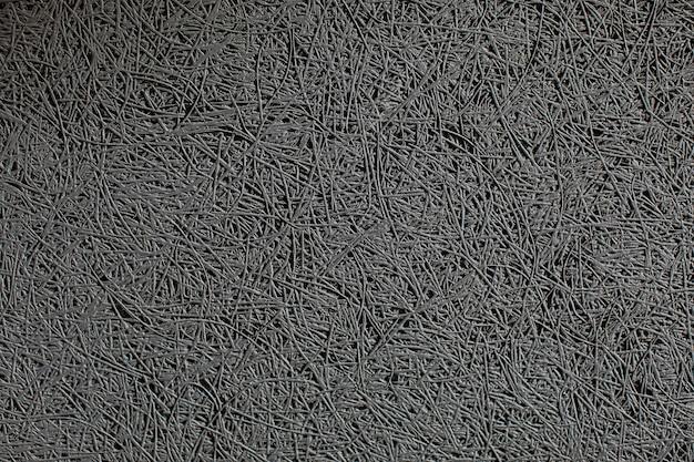 Feche a textura de uma parede com um painel de absorção de som cinza montado nele