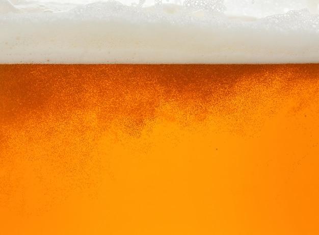 Feche a textura do fundo da cerveja lager com bolhas e espuma, despejando no vidro, ângulo baixo, vista lateral