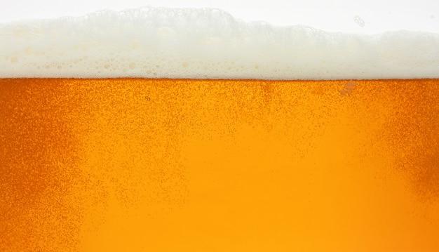 Feche a textura do fundo da cerveja lager com bolhas e espuma