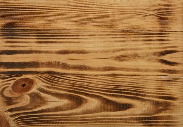 Feche a textura do fundo da superfície da madeira de pinho vintage queimada e escovada com nós e manchas