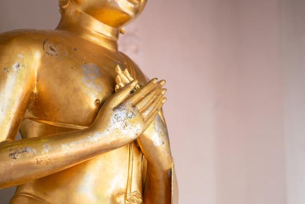 Feche a velha estátua de buda com cru de latão. mão da estátua de buda com carimbo de duas mãos com peito. acredite, cultura, tradicional. os budistas acreditam e merecem. conceito de calma e meditação. copie o espaço.