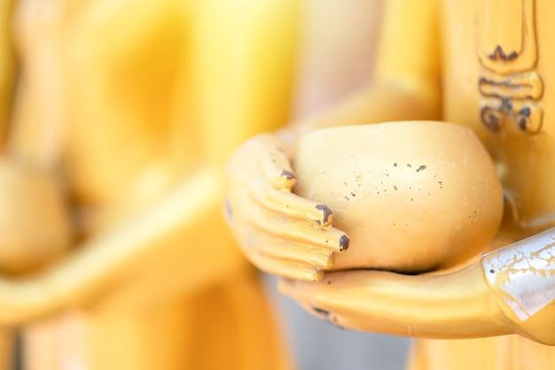 Feche a velha estátua de buda com cru de latão. mão da estátua de buda segurando a tigela de esmolas de monge com linha. acredite, cultura. os budistas acreditam e merecem. conceito de calma e meditação. copie o espaço.