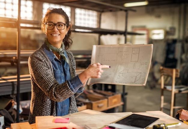 Feche a vista da mulher trabalhadora profissional focada feliz trabalhadora engenheiro apontando em um projeto de plantas na oficina de tecido ensolarado.