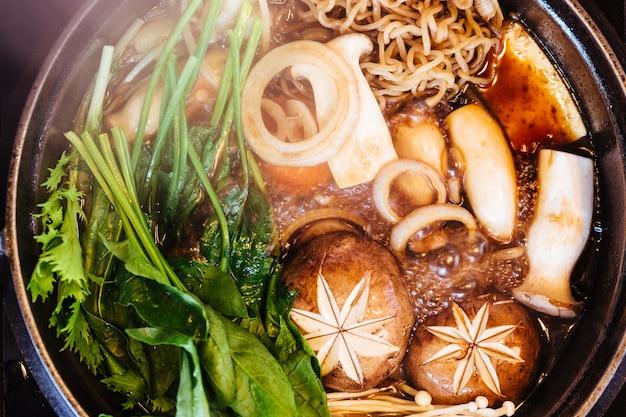 Feche a vista de cima da panela quente sukiyaki com vegetais ferventes, incluindo repolho, macarrão konjac, cebola, cenoura, shiitake, enokitake e tofu na sopa ao molho shoyu.