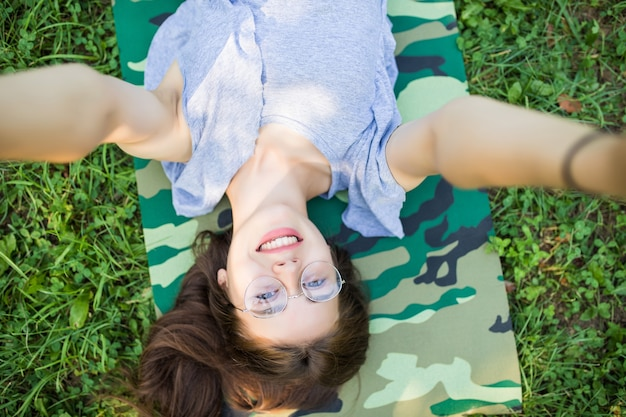 Feche a vista de cima de uma mulher morena rindo de óculos, deitada na grama no parque e fazendo selfie