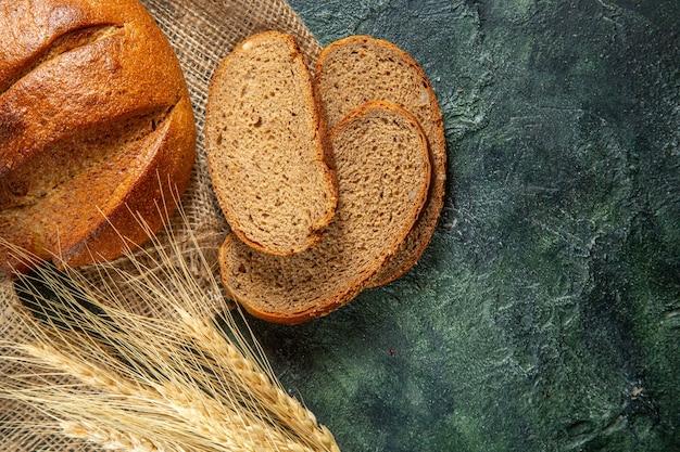 Feche a vista de todo e corte o pão preto dietético e os espinhos na toalha marrom na superfície de cores escuras