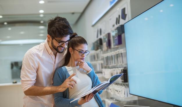 Feche a vista do atraente jovem animado feliz hipster amor jovem casal abraçado na frente da grande tv inteligente enquanto garota segurando a especificação em uma loja de tecnologia.