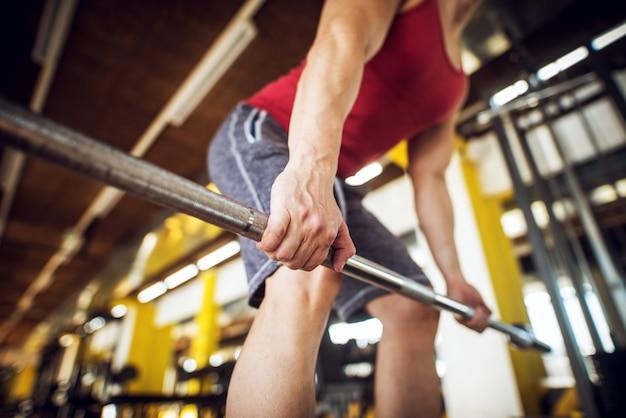 Feche a vista do foco da barra enquanto homem forte jovem fisiculturista muscular agachado e fazendo exercício traseiro no ginásio ensolarado moderno.