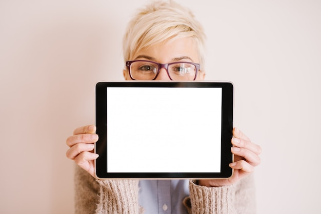 Feche a vista do foco de um tablet na posição horizontal com uma tela editável branca enquanto uma mulher bonita segurando-o.