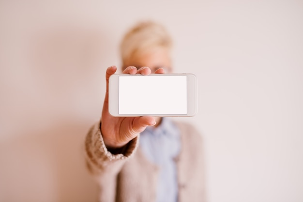 Feche a vista do foco do celular na posição horizontal, com uma tela editável branca, enquanto uma mulher turva segurando-o.