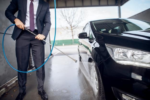 Feche a vista do foco do jovem empresário barbudo elegante bonito de terno limpando o carro com uma pistola de água na estação de lavagem manual de auto-serviço.
