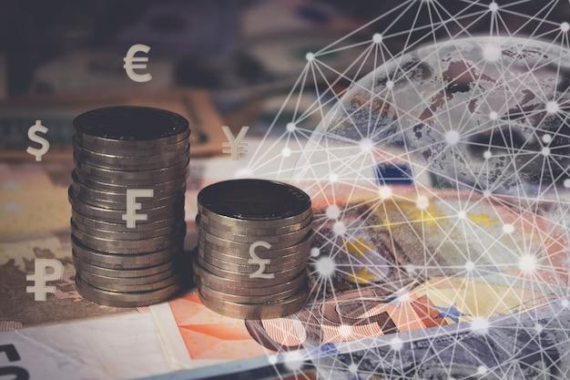 Feche a vista em perspectiva das notas de banco como pano de fundo. pilha de moedas, terra de holograma virtual, em fundo escuro, países diferentes de ícones de moeda. fechar-se. conceito de crescimento do negócio. risco financeiro.