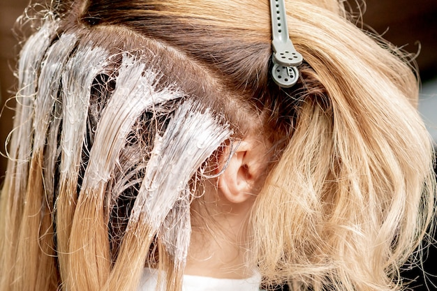 Feche a vista lateral da tintura no cabelo de uma mulher em um salão de cabeleireiro.