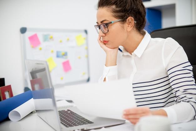 Feche a vista lateral de uma mulher entediada profissional bonita elegante, sentada no escritório na frente de um laptop com papel na mão.
