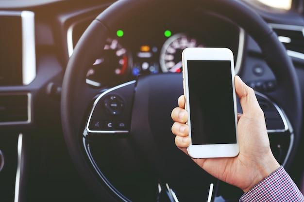 Feche a vista mão satisfeito jovem empresário olhando para o telefone móvel inteligente enquanto dirige um carro.