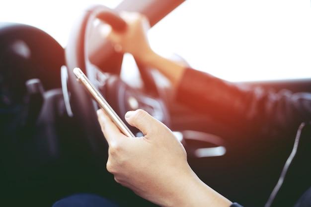 Feche a vista mão satisfeito jovem empresário olhando para o telefone móvel inteligente enquanto motorista de carro. transporte e conceito de veículo.