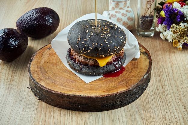 Feche a vista no hambúrguer saboroso e suculento com um pão preto com queijo e carne, molho de cranberry e carne em uma placa de madeira.