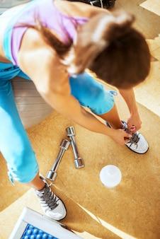 Feche a vista superior da jovem forma ativa garota com rabo de cavalo amarrando cadarços enquanto está sentado na bola de fitness no ginásio.