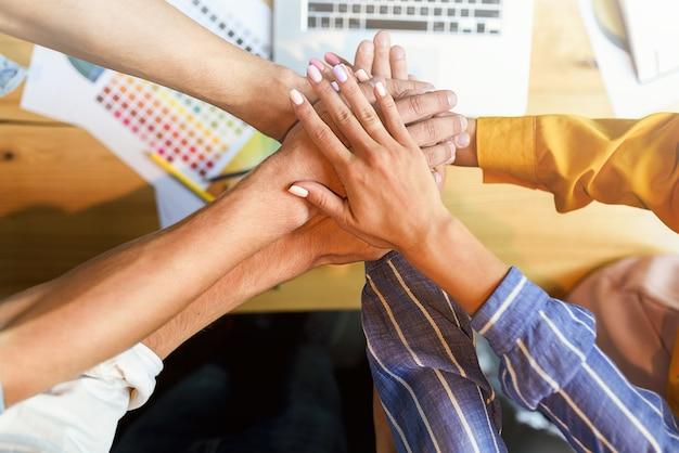 Feche a vista superior de jovens empresários, juntando as mãos.