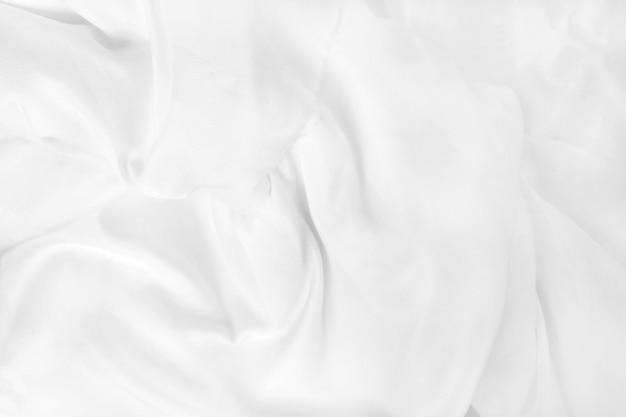 Feche a vista superior do lençol branco da cama e enrugue o cobertor bagunçado no quarto depois de acordar de manhã.
