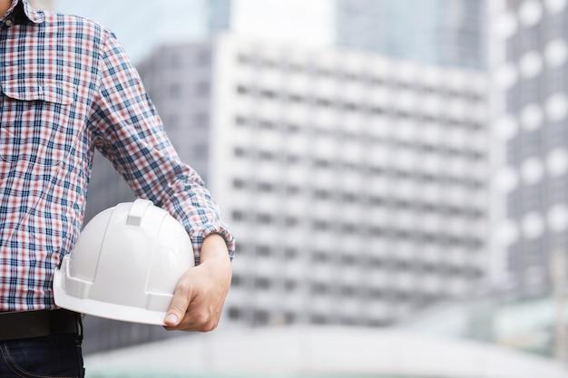 Feche a vista traseira do estande do trabalhador da construção civil masculino segurando o capacete amarelo de segurança e use roupas reflexivas para a segurança da operação de trabalho. exterior do edifício.