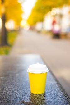 Feche a xícara de café de papel café amarelo no jardim no parque outono. foto de alta qualidade