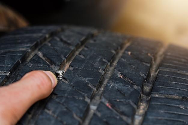 Feche acima da aderência no pneu, pneu furado o pneu está escapando da unha pode um pneu ser reparado