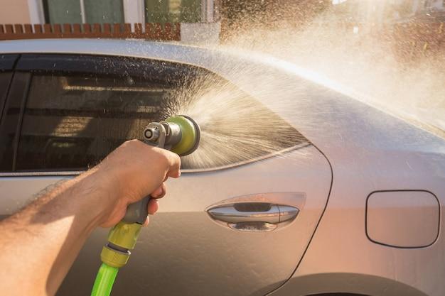 Feche acima da água de pulverização da mão para a lavagem de carros. lavagem de carros particulares. foco na pistola