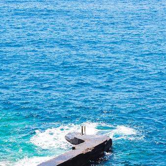 Feche acima da água ondulada cristalina na beira-mar