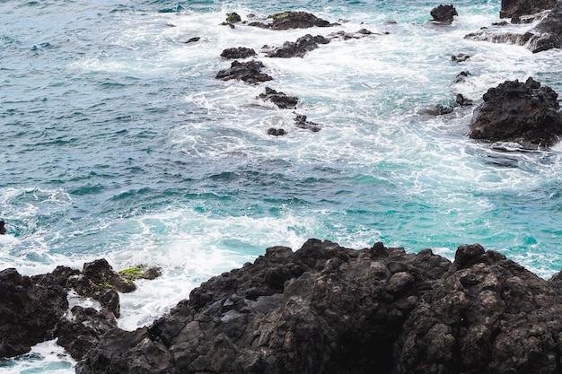 Feche acima da água ondulada na costa rochosa