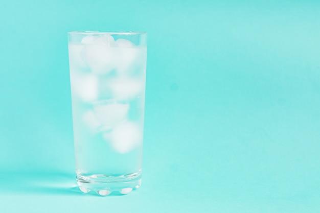 Feche acima da água pura com gelo no vidro transparente alto com espaço da cópia.