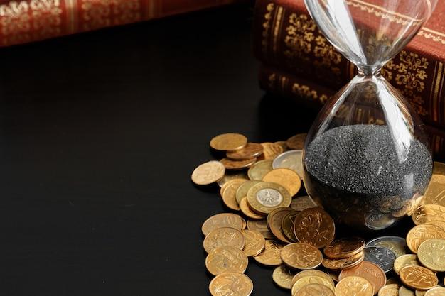 Feche acima da ampulheta com moedas de dinheiro