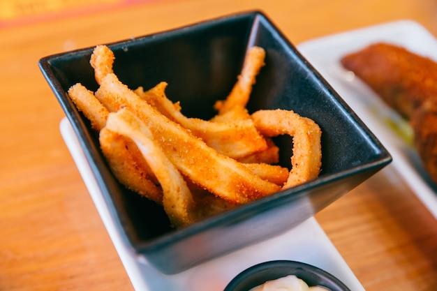 Feche acima da bacia do quadrado preto da vitória do calamari (prato fritado do calamar) servido.