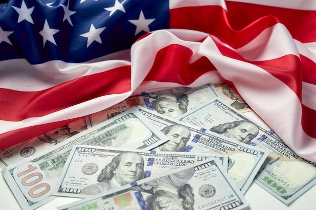 Feche acima da bandeira americana e do dólar em dinheiro. notas de dólar e fundo da bandeira dos estados unidos. economia dos eua