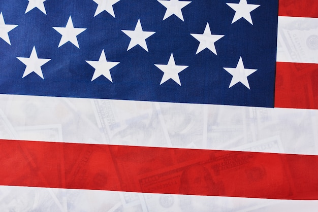Feche acima da bandeira americana sobre muitas notas de dólar do usd. financeiro