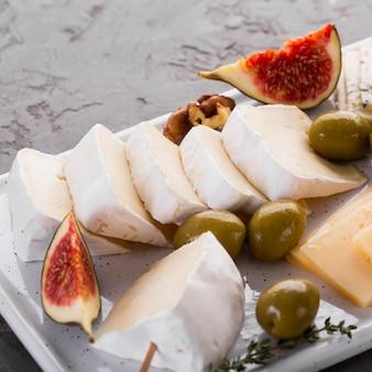 Feche acima da bandeja de sortimento de queijo com figo