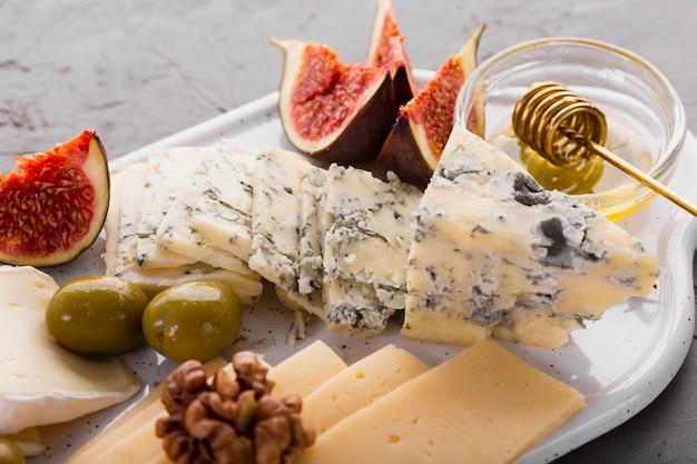 Feche acima da bandeja de sortimento de queijo com mel