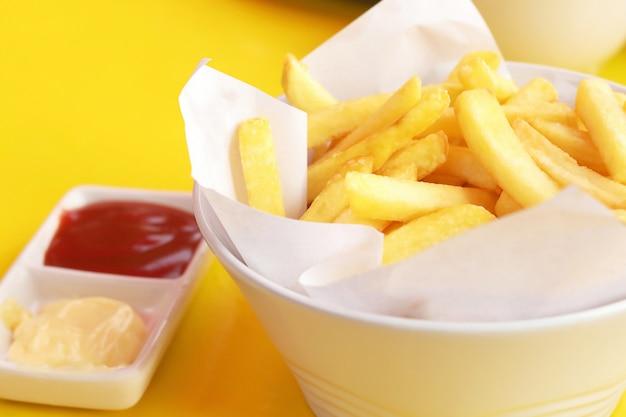 Feche acima da batata frita, batatas fritas com ketchup e maionese.