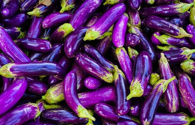 Feche acima da beringela ou da beringela roxas longas orgânicas no mercado